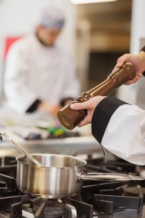 Pfeffer wird die Suppe im Topf von Küchenchef hinzugefügt