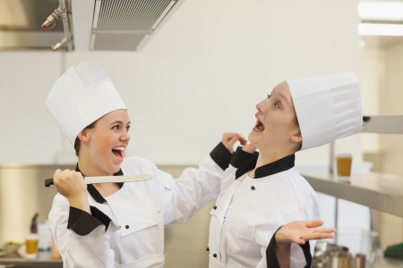 joking: Two Chefs joking and having fun in the kitchen with a knife