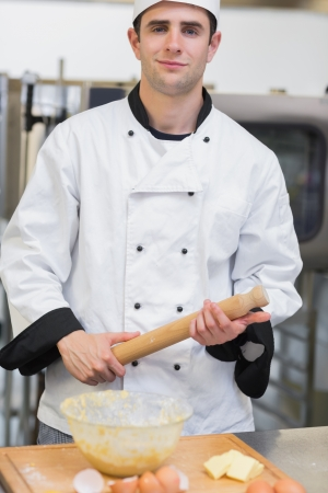 Baker holding a rolling pin while smiling in kitchen photo