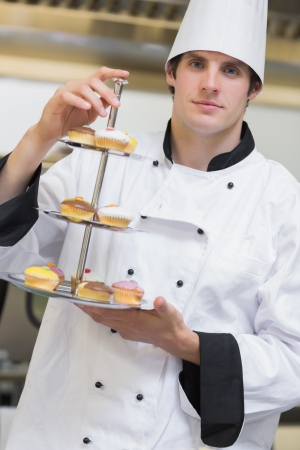 chefs whites: Baker presenting tiered cake tray in the kitchen Stock Photo