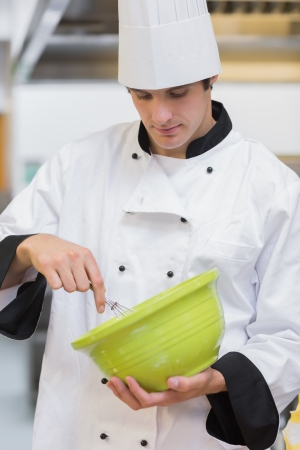 whisking: Chef whisking batter in green mixing bowl in kitchen Stock Photo