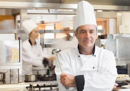 chef cocinando: Chef sosteniendo la cuchara mientras sonre�a