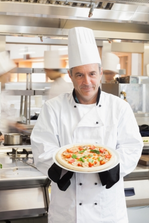 Chef smiling and showing pizza in busy kitchen photo