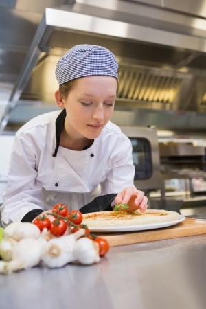 Female cook preparing pizza on counter in kitchen photo
