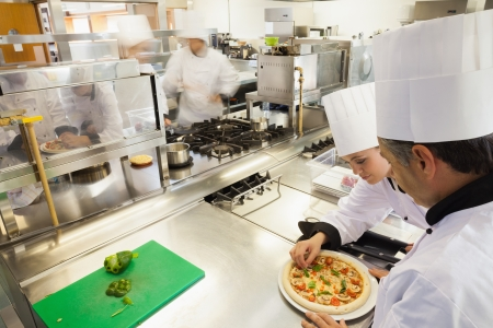Cooks preparing pizza in busy kitchen photo