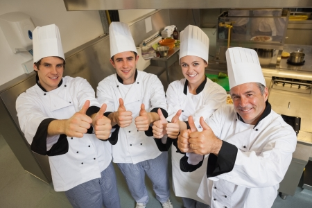 chefs whites: Team of Chefs giving thumbs up in restaurant kitchen