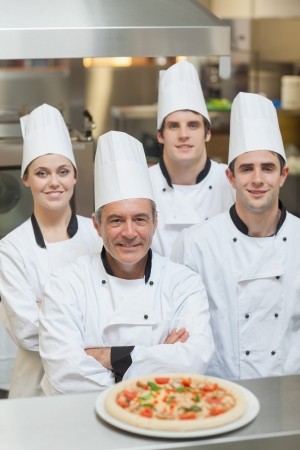 Smiling group of Chefs with a pizza on the counter photo