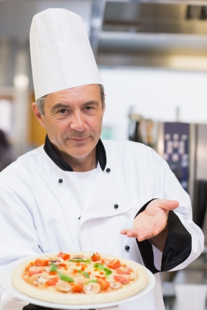 chef italiano: Cocinero orgulloso mostrando su pizza en la cocina