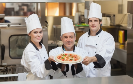 Three Chefs holding a pizza while smiling photo