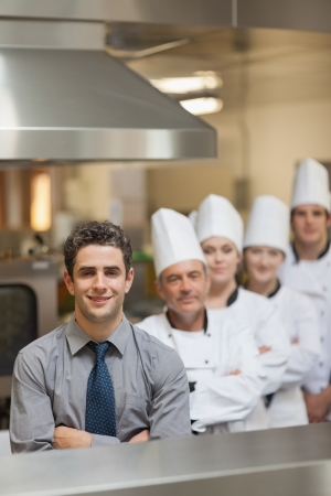Waiter and Chefs standing in kitchen photo