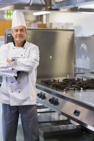 Chef smiling while standing at stove in the kitchen photo