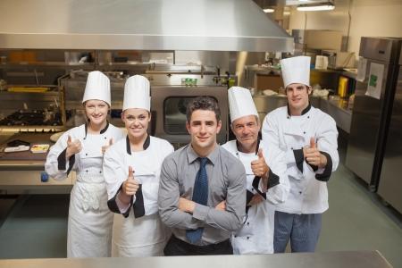 meseros: Cinco trabajadores restauran con chef que da los pulgares para arriba Foto de archivo
