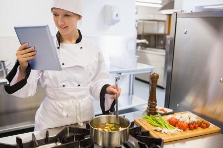 bulion: Kobieta kucharz użyciu komputera typu Tablet podczas gotowania zupy Zdjęcie Seryjne