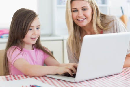 Little girl typing on laptop with her mother next to her in the kitchen photo