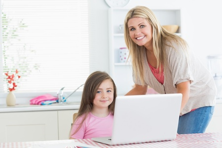 Mother and child in the kitchen smiling with a laptop photo