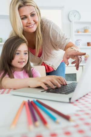 Mother pointing at laptop with daughter sitting down in the kitchen photo