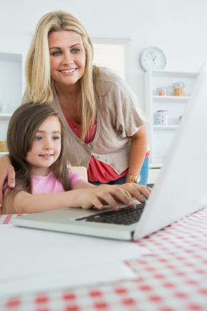 Little girl typing with mother watching at laptop in kitchen photo