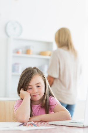 Little girl bored with drawing with mother in background photo