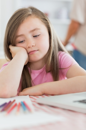 Girl sitting while looking bored with paper and colouring pencils in kitchen photo