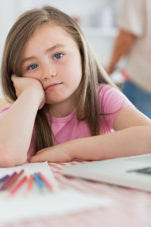 Girl sitting at kitchen table looking bored with paper and colouring pencils photo