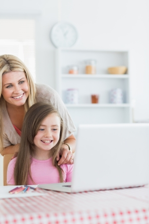 Laughing mother and girl looking at laptop in the kitchen photo