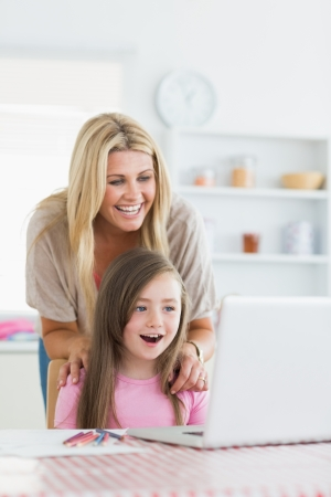 Woman and daughter sitting at the table at the kitchen both smiling at the laptop photo