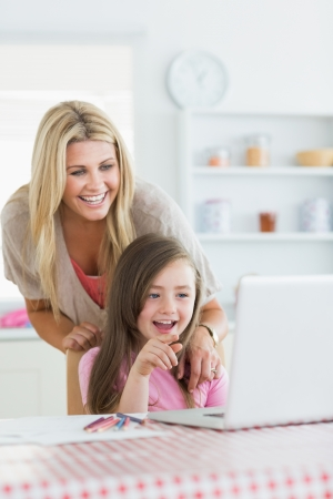 Mother and child laughing at laptop with child pointing in the kitchen photo