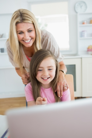 Little girl pointing at laptop and laughing with mother in the kitchen photo