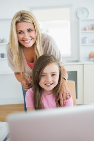 Woman and daughter smiling at the laptop in the kitchen photo