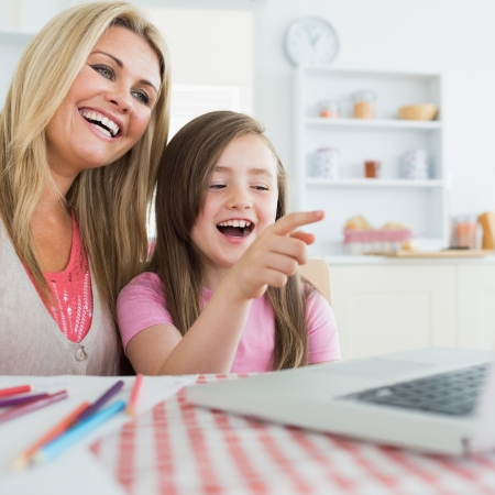 Mother and daughter laughing at laptop in the kitchen photo