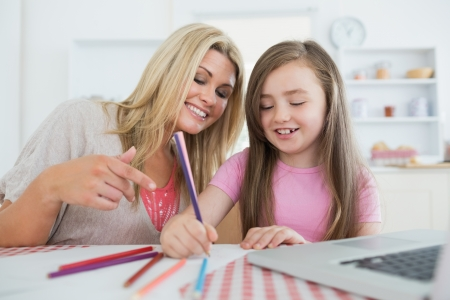 Mother and daughter drawing together at the kitchen  photo