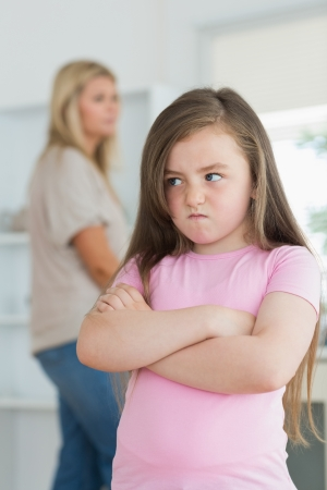 angry: Little girl looking angry in the kitchen with mother in background Stock Photo