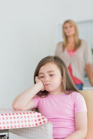 exasperated: Little girl is sitting while looking exasperated at kitchen table wth mother in background