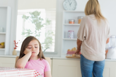 Child falling asleep at kitchen table with mother working on counter photo