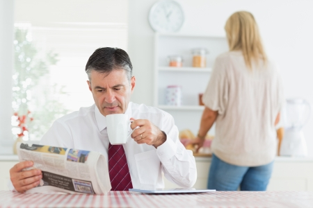 Man sitting at the kitchen table while reading a newspaper and holding a cup of coffee before work photo
