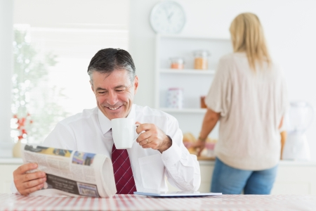Man smiling while reading newspaper before work in kitchen drinking coffee photo