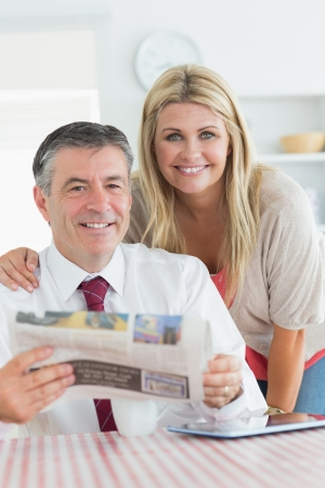 Smiling couple with newspaper and tablet pc in the kitchen before work photo