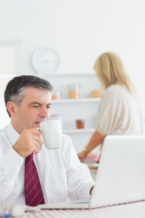 Man drinking coffee while checking laptop in kitchen before work photo