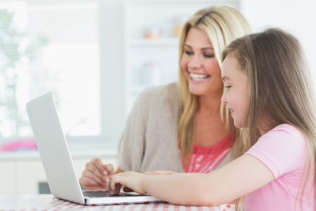 Woman and daughter sitting at the laptop at the kitchen  photo