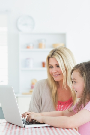 Mother and little girl sitting at the kitchen smiling with laptop  photo