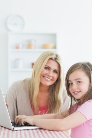 Mother and daughter sitting at the kitchen while smiling with a laptop together photo
