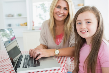 Woman typing at the laptop sitting next to her daughter in the kitchen photo