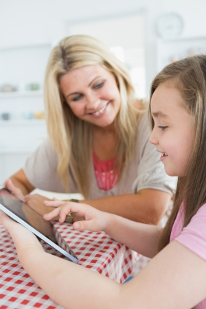 Woman and daughter holding a tablet pc while smiling at the kitchen table photo
