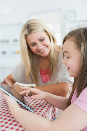 Mother and little girl using a tablet pc while smiling in the kitchen photo