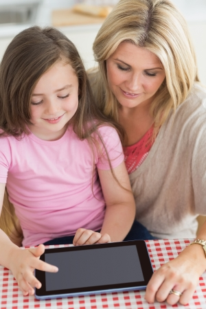 Child using tablet pc with mother at kitchen table photo
