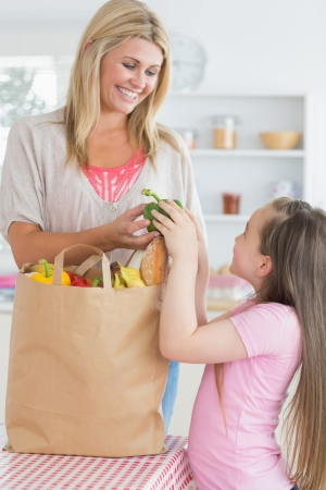 Woman giving green pepper to daughter from grocery bag in the kitchen photo