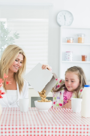 Mother and daughter having cereal at breakfast photo