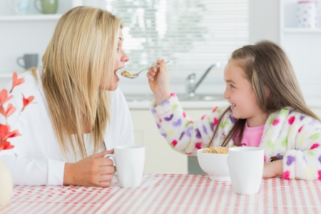 Girl feeding her mother at the kitchen  photo