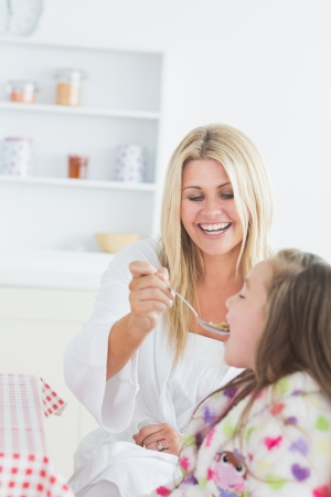 Mother feeding her child cereal at the kitchen  photo