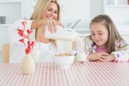 Woman pouring milk into a glass for daughter and smiling  photo